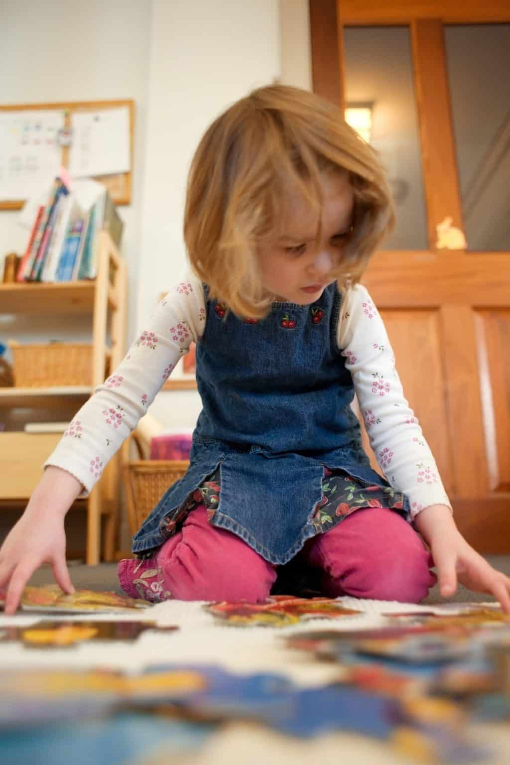 An intent 4-year-old girl in a Montessori classroom